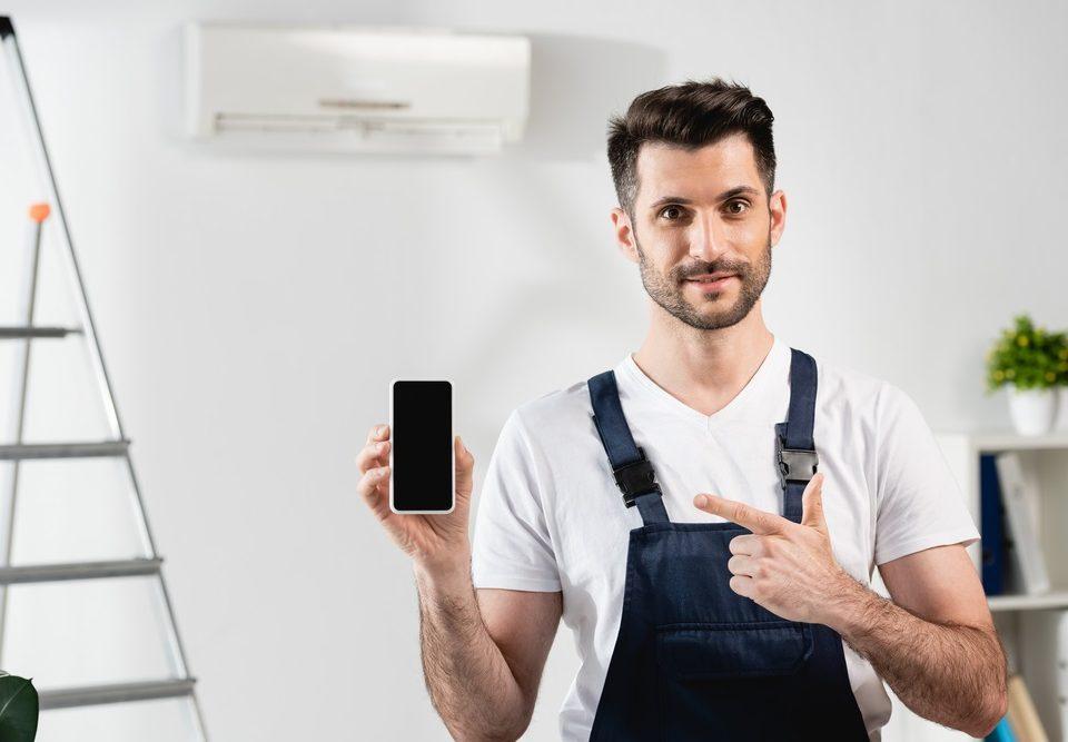 Reparador sonriente apuntando al telefono inteligente
